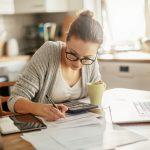 controle de contas a pagar - mulher fazendo contas na mesa da sua casa