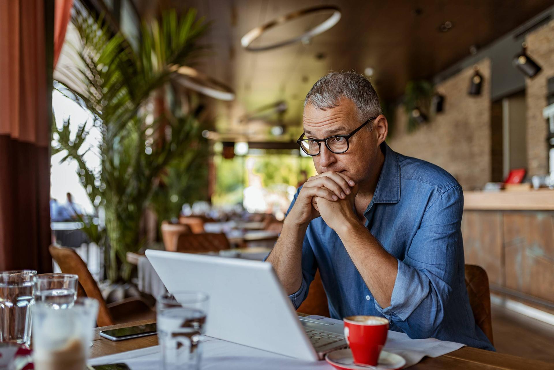 clientes inadimplentes - homem de meia idade sentado em frente a um computador com as mãos escorando o rosto, pensativo