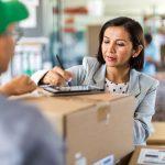 logística para e-commerce - mulher recebeendo caixa de um entregador