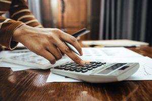 elisão fiscal - pessoa utilizando calculadora para pagar impostos corretamente