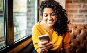 instagram shopping - mulher sorrindo acessando redes sociais através do smartphone