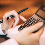 planejamento fiscal - pessoa segurando calculadora e fazendo contas