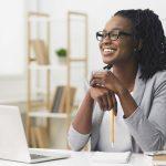 ponto de equilíbrio - mulher em um escritório sorrindo em frente a um notebook