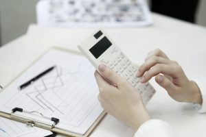 saúde financeira da empresa - pessoa fazendo cálculos financeiros em uma calculadora