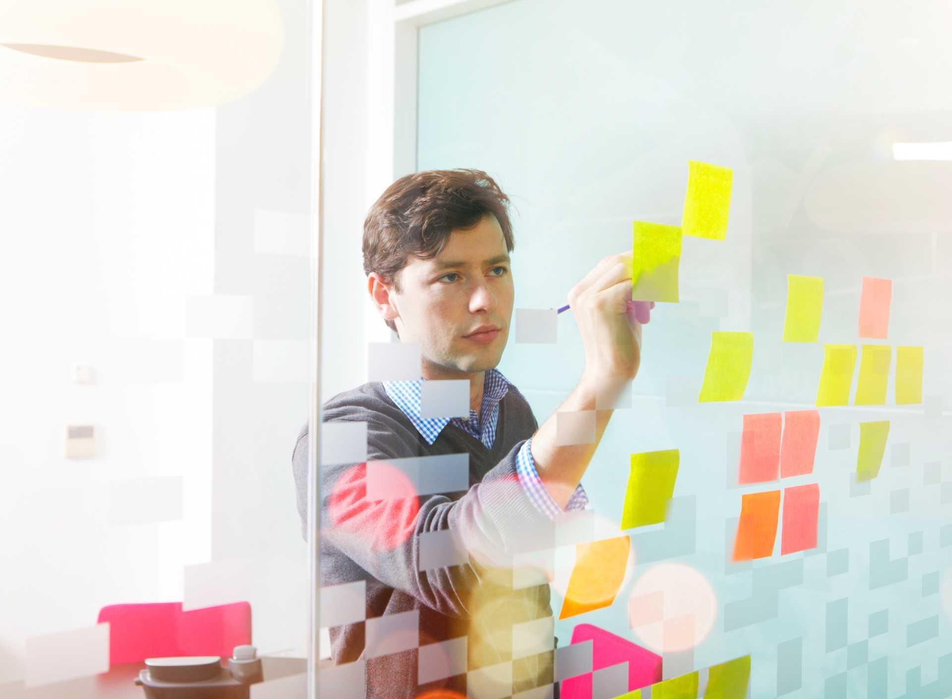 gestão à vista - gestor da empresa atualizando dados em post-its colados numa parede de vidro