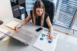 indicadores gerenciais - mulher avaliando dados e gráficos de desempenho da loja de móveis