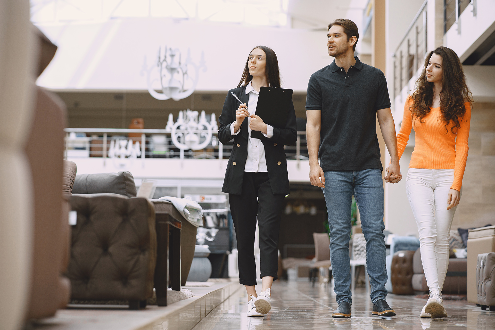 objeção de vendas - casal em uma loja de móveis considerando comprar móveis acompanhados de uma vendedora