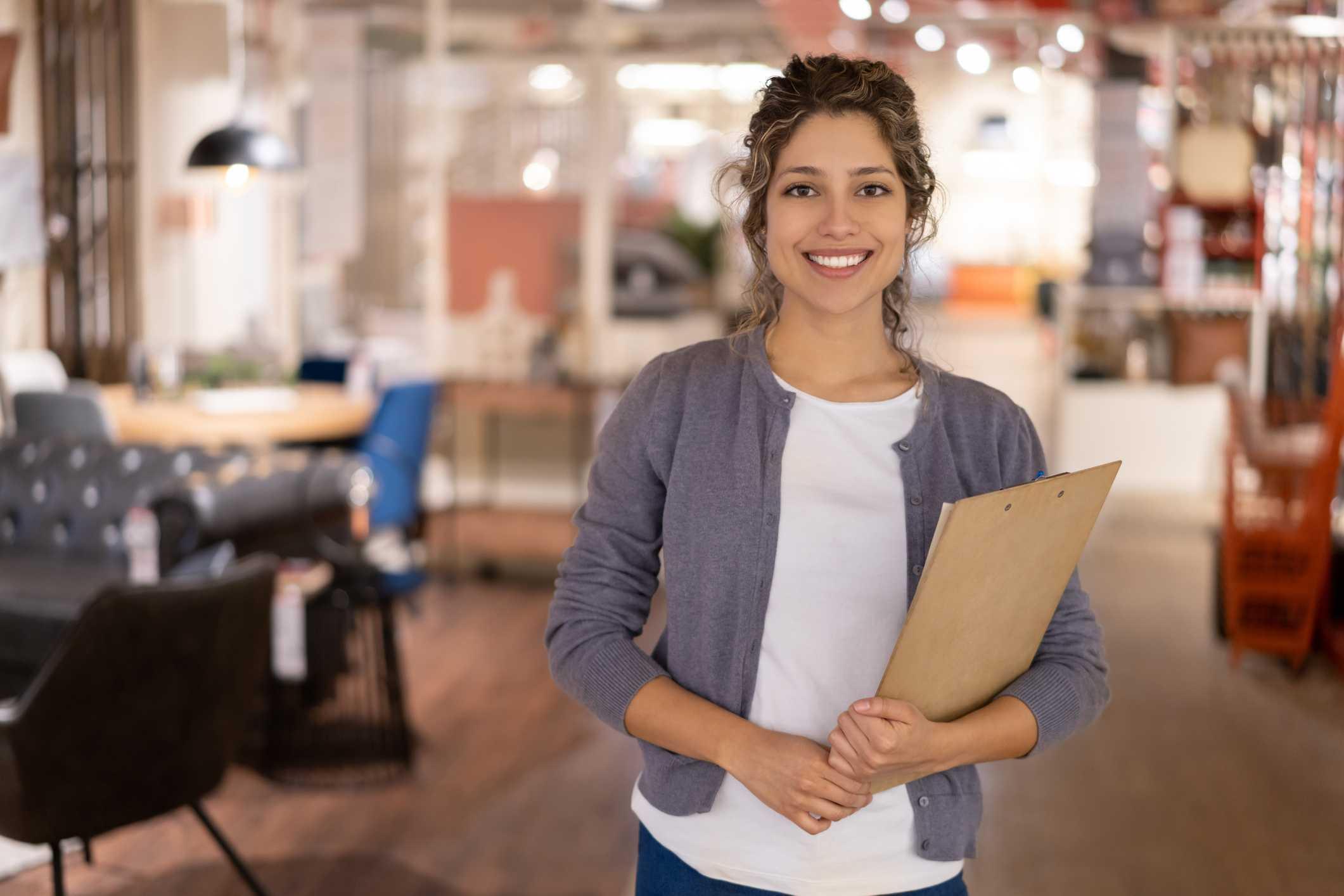 venda técnica - vendedora em uma loja de móveis sorrindo segurando uma prancheta