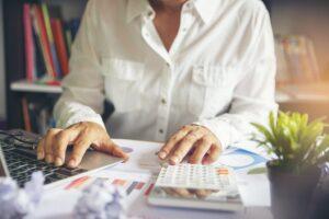 gestão de custos - pessoa fazendo cálculos em uma mesa de escritório