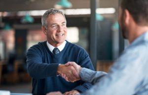 gestão profissionalizada - homem mais velho e homem mais jovem dando aperto de mão